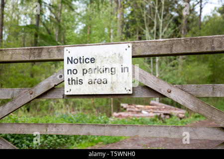 Landscape close up of No Parking sign on wooden gate outdoors in UK woodland area. - Stock Photo
