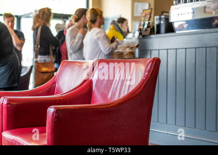 Red chairs in Coffee #1, a branch of small coffee house chain, on Chepstow Beaufort Square. Wales. - Stock Photo