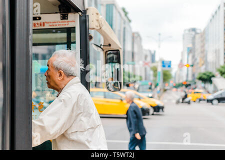 Elderly taking a taiwanese bus in Taipei city during a morning rush hour - Stock Photo