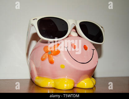 Close up of pink piggy bank with sun glasses - Stock Photo