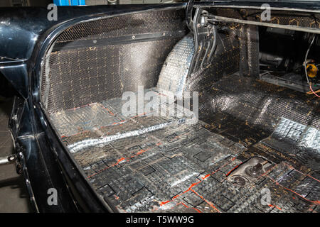 Tuning the car in a sedan body with three layers of noise insulation of the trunk. Audio and vibration isolation. Soft material. Dismantled car. Addit - Stock Photo