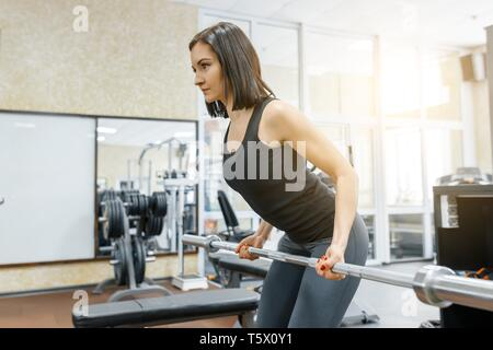 Young beautiful athletic woman brunette doing fitness exercises in the gym. Fitness, sport, training, people, healthy lifestyle concept