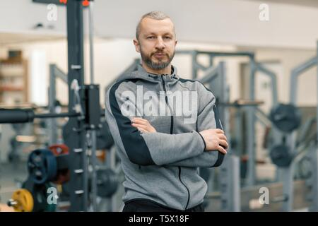 Portrait of sporty man with folded hands in the gym, handsome bearded trainer looking at the camera. - Stock Photo