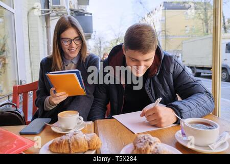 Young couple of students study in outdoor cafe, drink coffee tea, eat croissants, background is spring city street. - Stock Photo