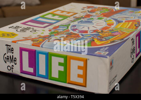 'RAK, RAK, UAE - 4/20/2019 : Colourful Game of Life Box set out on the table for some family fun for all ages strategizing with this Milton Bradley cl - Stock Photo