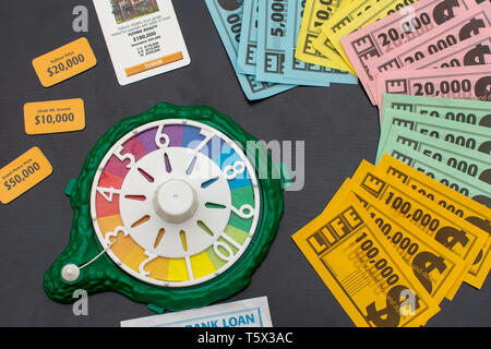 'RAK, RAK, UAE - 4/20/2019 : Top view of colourful Game of Life  Money fanned out on the table and set-up materials. Family fun for all ages strategiz - Stock Photo