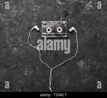 Conceptual photo illustrating the love of music. Audio cassette and headphones on a black concrete background. Top view. - Stock Photo