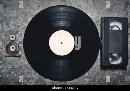 Vinyl record, audio and video cassettes on a gray concrete surface. Retro media technology from the 80s. Top view. - Stock Photo