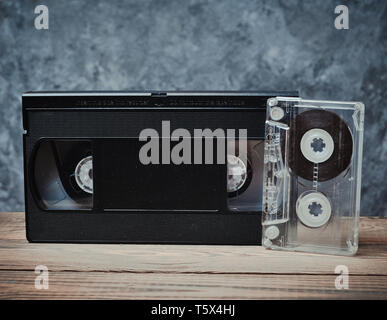 Audio and video cassette close-up on a wooden shelf against a gray concrete wall. Retro technology for listening to music and watching videos. - Stock Photo