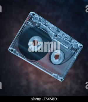 Audio cassette levitation. Retro media technology from the 80s. Mystical light. - Stock Photo