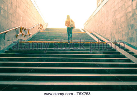 woman climbs the stairs to a bright light at the end of the tunnel. toned - Stock Photo