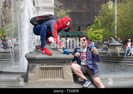 A young man in Washington Square Park taking a selfie with a performance artist dressed in a Spiderman costume. In New York City. - Stock Photo