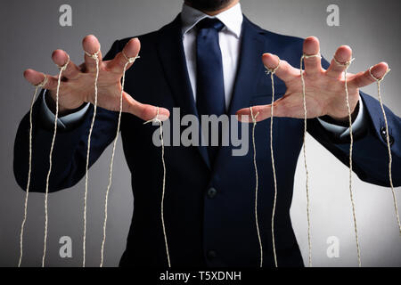Man's Hand Controls The Puppet With The Fingers Attached To Threads Against Gray Background - Stock Photo