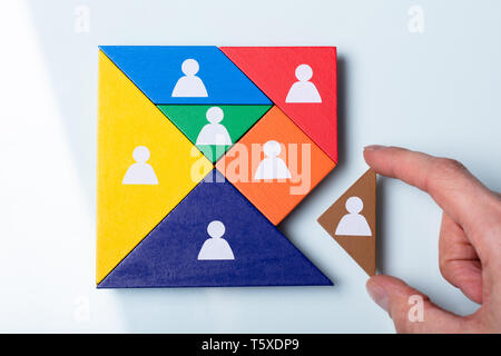 An Overhead View Of Person's Hand Holding A Missing Piece In A Square Tangram Puzzle - Stock Photo