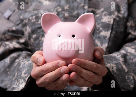 Close-up Of Soldier's Hand Holding Pink Piggy Bank - Stock Photo