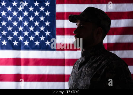 Close-up Of Male Solider Standing In Front Of An Us Flag - Stock Photo