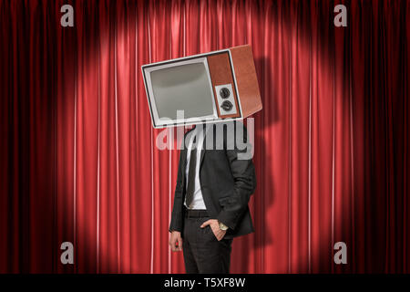 Businessman with vintage tv set instead of head on red stage curtains background - Stock Photo
