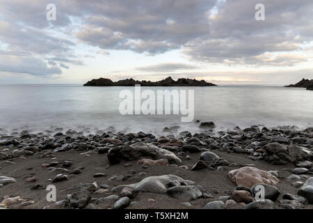 Seascape looking west at dawn from the shoreline on the coast of Alcala, long exposure photography, Tenerife, Canary Islands, Spain - Stock Photo