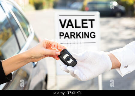 Woman's Hand Giving Car Key To Male Valet Near Valet Parking Sign - Stock Photo