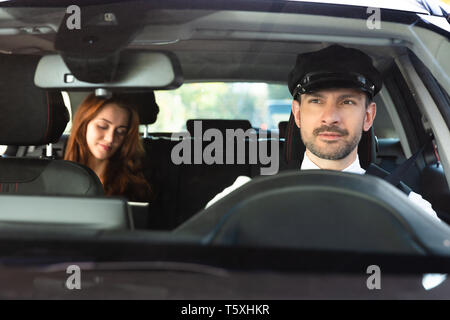 Portrait Of A Smiling Male Chauffeur Driving Car With Businesswoman - Stock Photo