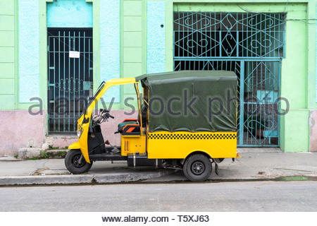 Santa Clara, Villa Clara, Cuba-March 27, 2019: A yellow rickshaw (known as 'motoneta' in the island) parked on a city sidewalk.  They are a popular mo - Stock Photo