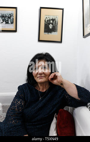 Tirana, Albania-April 13,2019: Owner of a typical Albanian restaurant poses at her premises for a foreign client. - Stock Photo