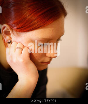Young pretty ginger girl looking surrowful and sad on the table - Stock Photo