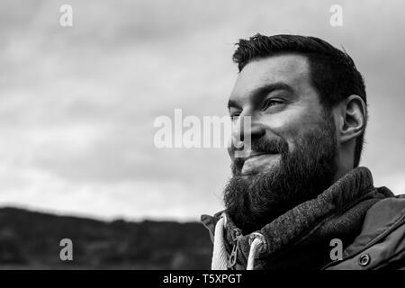 Young attractive bearded man with dark hair and a pullover in the park smiling - Stock Photo