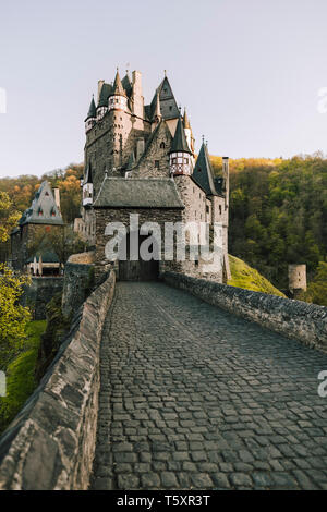 sunset view of Burg Eltz castle at Rhineland-Palatinate, Germany, a medieval castle located on a hill in the forest, construction started prior to 115 - Stock Photo
