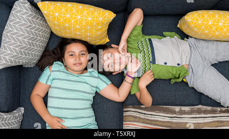Mixed asian/caucasian brother and sister laying on sofa together smiling looking directly at camera. Stock Photo