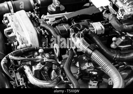 Car gasoline engine. Car engine part. Close-up image of an internal combustion engine. Engine detailing in a new car. Black and white - Stock Photo