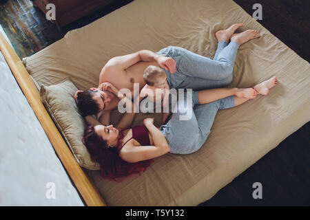 happy young parents with baby in the bed at home.