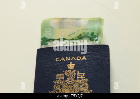 Canadian passport laying on top of twenty dollar bills. Concept of immigrating or emigrating, or travelling with a canadian passport. - Stock Photo