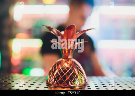 metal glasses of fresh summer cocktails decorated with fruit and fume on the bar counter. - Stock Photo