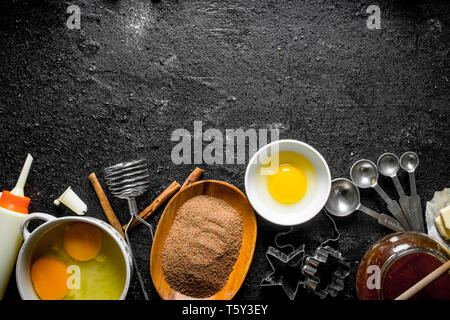 Baking background. Preparation of homemade dough. On black rustic background - Stock Photo