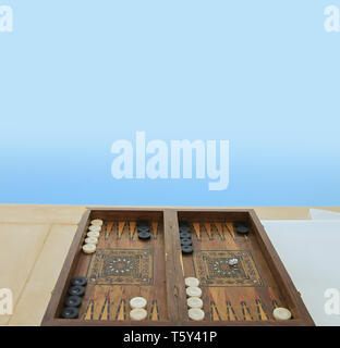 Wooden Antique Backgammon Game Board Isolated near swimming pool. Stock Image. - Stock Photo