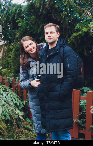 Large decorated Christmas tree with young couple standing near. - Stock Photo