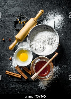 Baking background. Flour with honey, cinnamon and egg. On black rustic background - Stock Photo