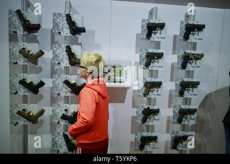 Indianapolis, Indiana, UK. 27th Apr, 2019. A boy looks at hand guns in the Sig Sauer booth during the third day of the National Rifle Association convention. Credit: Jeremy Hogan/SOPA Images/ZUMA Wire/Alamy Live News - Stock Photo