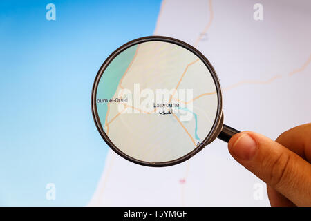 Laayoune, Western Sahara. Political map. City visualization illustrative concept on display screen through magnifying glass in the hand. - Stock Photo