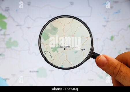 Bamako, Mali. Political map. City visualization illustrative concept on display screen through magnifying glass in the hand. - Stock Photo