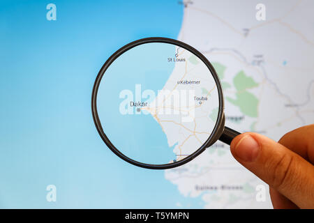 Dakar, Senegal. Political map. City visualization illustrative concept on display screen through magnifying glass in the hand. - Stock Photo