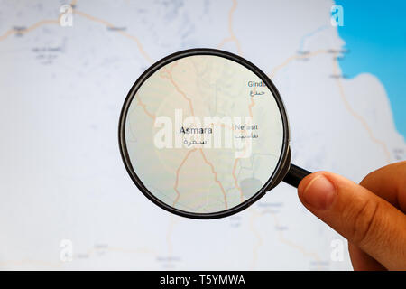 Asmara, Eritrea. Political map. City visualization illustrative concept on display screen through magnifying glass in the hand. - Stock Photo