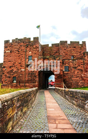 A wide cobblestone path paved along its centre with flagstones leads through the archway of De Ireby's Tower in the centre of the south curtain wall - Stock Photo