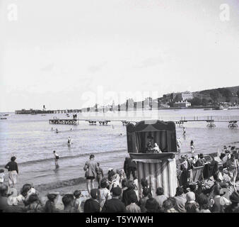 1940s, historical, people watching a traditional punch and judy puppet show on the beach at Swanage, England, UK. - Stock Photo