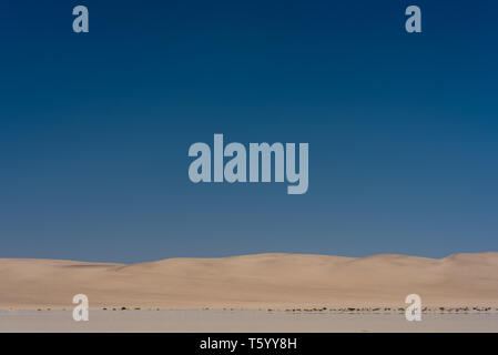 Coastal Sand Dunes under a large blue sky  near Walvis Bay, Namibia - Stock Photo