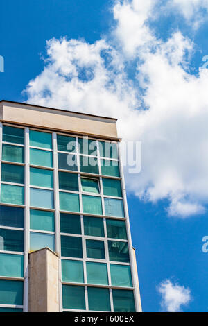 A building glass wall partial view against a beautiful cloudy summer sky in Haskovo, Bulgaria - Stock Photo