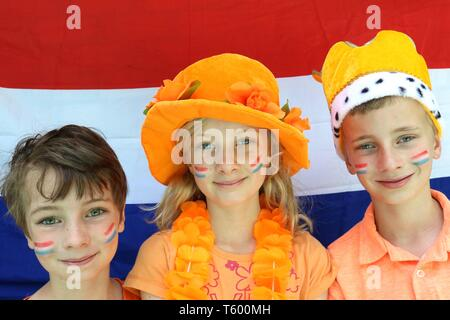Three dutch children dressed up in orange in front of flag of the Netherlands - Stock Photo