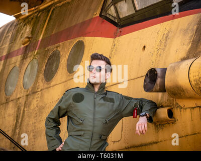 A handsome young man pilot in a green overall standing next to an old plane on a sunny day. - Stock Photo