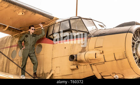 A handsome young man pilot in a green overall standing on the wing of an old plane on a sunny day. - Stock Photo